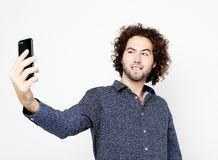 Portrait of a cheerful  man taking selfie over white background. Tehnology, emotion and people concept: Portrait of a cheerful  man taking selfie over white royalty free stock image