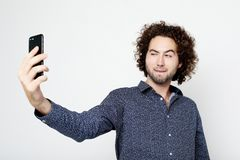 Portrait of a cheerful man taking selfie over white background. Tehnology, emotion and people concept: Portrait of a cheerful man taking selfie over white stock images