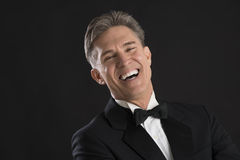 Portrait Of Cheerful Man In Tuxedo Laughing. Portrait of cheerful mature man in tuxedo laughing against black background Stock Photos