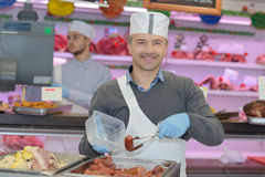 Portrait cheerful mature male butcher in butchery Stock Images