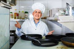 Portrait of cheerful mature man cook with frying pans on kitchen Stock Images