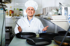 Portrait of cheerful mature man cook with frying pans on kitchen Stock Image