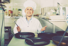 Portrait of cheerful mature man cook with frying pans on kitchen Royalty Free Stock Photos