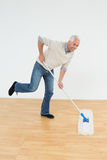 Portrait of a cheerful mature man mopping the floor Stock Images