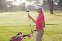 Portrait of cheerful mature woman carrying golf club Royalty Free Stock Image