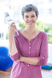 Portrait of cheerful mature woman holding water bottle Royalty Free Stock Image