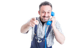 Portrait of cheerful mechanic with telephone pointing you Royalty Free Stock Photo