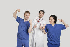 Portrait of a cheerful medical team gesturing over gray background Royalty Free Stock Photo