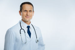 Portrait of cheerful medical worker with stethoscope. Support is what really matters. Positive minded mature doctor wearing a white coat looking into the camera royalty free stock image