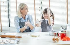 Portrait of cheerful mother and cute daughter prepare dough for baking cookie sitting at the table in the kitchen looking at each. Other and having fun in the royalty free stock images