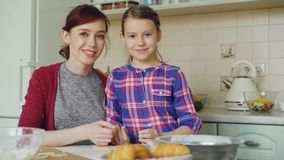 Portrait of cheerful mother and cute smiling daughter looking at camera while cooking in the kitchen on weekend. Family stock video footage