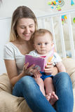 Portrait of cheerful mother reading book to her baby boy at livi Stock Photos