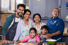 Portrait of cheerful multi-generation family enjoying in kitchen. Portrait of cheerful multi-generation family enjoying while preparing food in kitchen at home stock photo