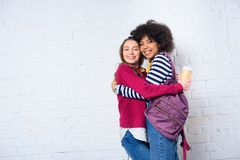 portrait of cheerful multicultural students hugging each other against white royalty free stock photography