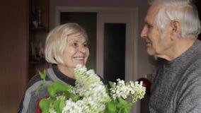 Portrait of a happy grandfather and grandmother. Grandpa kissing gandma