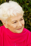 Portrait of a cheerful old lady over green background. Royalty Free Stock Photos