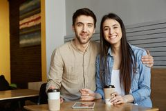 Portrait of cheerful perspective startupers pair with dark hair in casual clothes, sitting in cafe, smiling bright Stock Photo