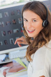 Portrait of a cheerful photo editor wearing a headset Royalty Free Stock Image