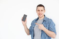 Portrait of a cheerful, positive, attractive guy with stubble in a shirt, with a smartphone with a black screen in his hand, point royalty free stock photos