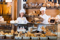 Portrait of cheerful positive couple at bakery display Stock Images