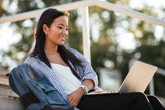 Portrait of a cheerful pretty asian female student. Holding laptop computer on her lap while sitting on the bench at the park Stock Photo