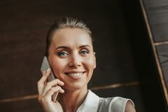Glad businesswoman talking on the phone indoor Royalty Free Stock Photography