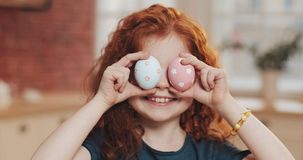Portrait of cheerful redhead little kid girl playing with easter egg on the kitchen background. She is cheering and stock photo
