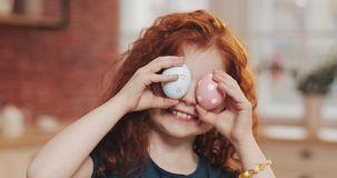 Portrait of cheerful redhead little kid girl playing with easter egg on the kitchen background. She is cheering and