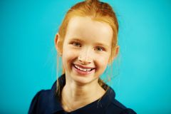 Portrait of cheerful redheaded school girl of seven years old on blue isolated background. Joyful child with genuine stock photos