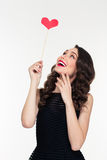 Portrait of cheerful retro styled young woman with heart booth Royalty Free Stock Photography