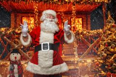 Happy new year. Portrait of cheerful Santa Claus in the courtyard of his house decorated with Christmas lights. Christmas and New Year concept stock image