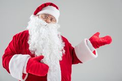 Joyful Father Frost gesturing to show something. Portrait of cheerful Santa Claus pointing arm sideways with confidence. He is standing in red and white costume Stock Image