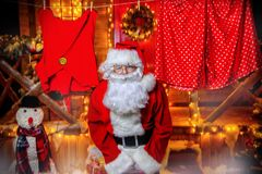 Portrait of cheerful santa. Claus in the courtyard of his house decorated with Christmas lights. Christmas and New Year concept royalty free stock image