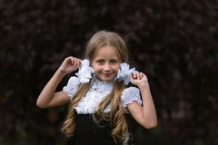 Portrait of cheerful schoolgirl girl with white bows royalty free stock photo