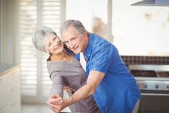 Portrait of cheerful senior couple dancing in kitchen Royalty Free Stock Photos