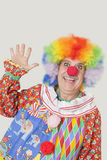 Portrait of cheerful senior male clown waving hand over gray background Royalty Free Stock Photos