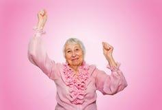 Portrait of a cheerful senior woman gesturing victory over pink. The portrait of a cheerful senior woman gesturing victory over pink background Stock Photo
