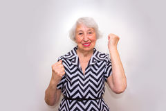 The portrait of a cheerful senior woman gesturing victory over pink. The portrait of a cheerful smiling senior woman gesturing victory over gray studio Royalty Free Stock Photo
