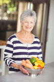 Portrait of cheerful senior woman holding colander with vegetables Stock Photo