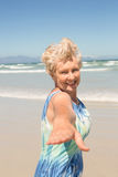 Portrait of cheerful senior woman standing against clear sky. At beach Royalty Free Stock Images