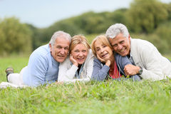 Portrait of cheerful seniors lying in grass Stock Photos