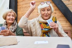 Happy Old Lady Winning Card Game. Portrait of cheerful seniors playing card game at lunch table on outdoor terrace, focus on two old women winning game royalty free stock photo