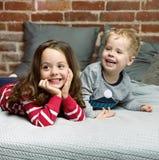 Portrait of cheerful siblings relaxing in bedroom stock photo