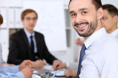 Portrait of cheerful smiling business man  against a group of business people at a meeting. Stock Photos