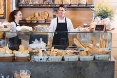 Portrait of cheerful smiling couple at bakery display Stock Photos