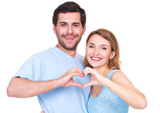 Portrait of cheerful smiling couple. Portrait of cheerful smiling couple standing together show hands heart - isolated on white background royalty free stock photo
