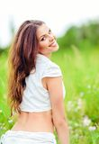 Portrait of cheerful smiling young woman in a field Royalty Free Stock Photography
