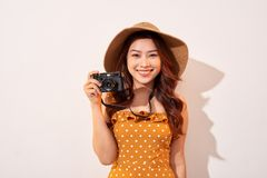Portrait of cheerful smiling young woman taking photo with inspiration and wearing summer dress. Girl holding retro camera. Model royalty free stock photo