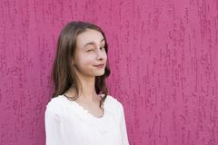 Joyful teenager posing outside. Portrait of cheerful smiling young woman in white blouse. Cute funny girl winks and looking at camera with happiness and gladness royalty free stock photography
