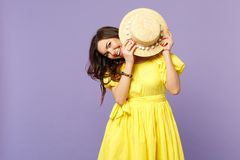 Portrait of cheerful smiling young woman in yellow dress covering face with summer hat  on pastel violet stock image